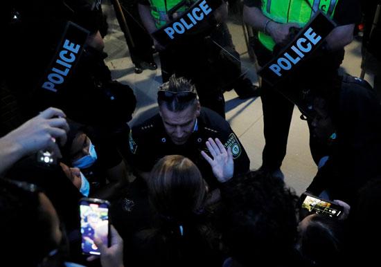 أحد أفراد الشرطة يتحدث مع متظاهرين فى بوسطن