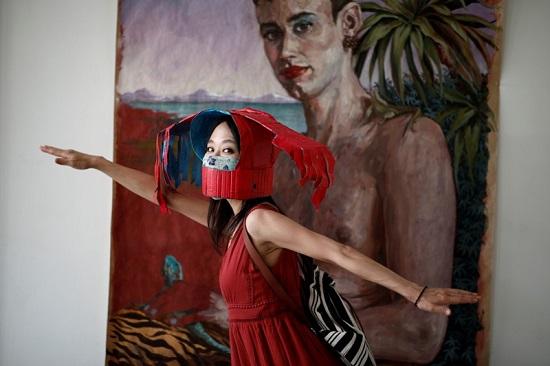 إحدى زائرات المعرض تتباهى بقبعتها المميزة