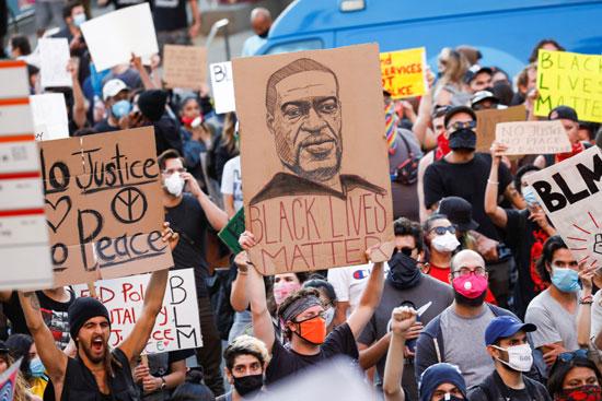 المتظاهرون يرفعون صوراً لجورج فلويد