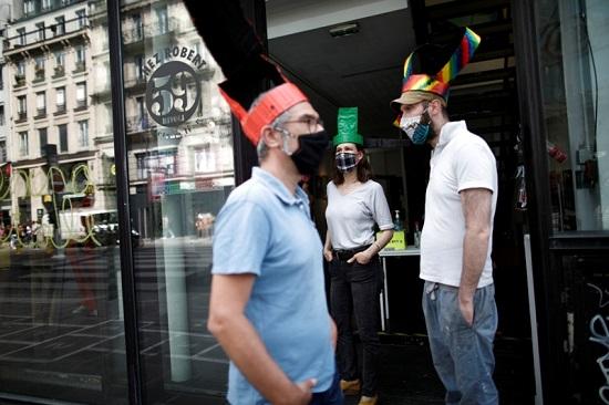 زوار المعرض يتحدثون معًا بالكمامات والقبعات