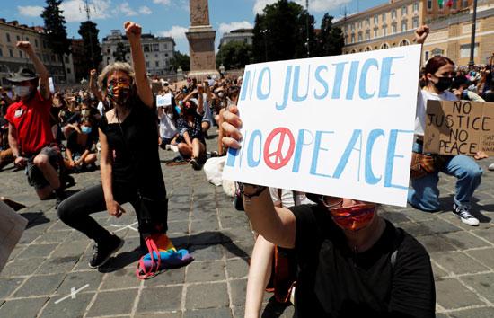 متظاهر يرفع لافتة للمطالبة بتحقيق العدالة