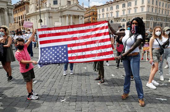 متظاهرون يرفعون علم أمريكا بشعارات ضد العنصرية