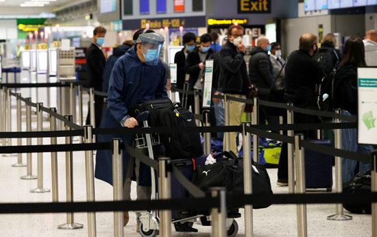 راكب يرتدى ماسك طبى خلال وقوفه بمطار مانشيستر