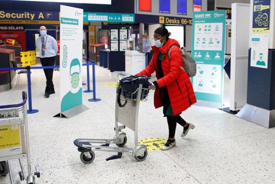 سيدة ترتدى الكمامة بمطار مانشيستر