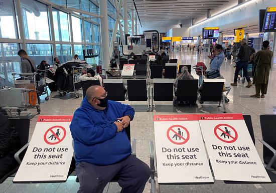 أحد المسافرين يجلس بمبنى مطار هيثرو