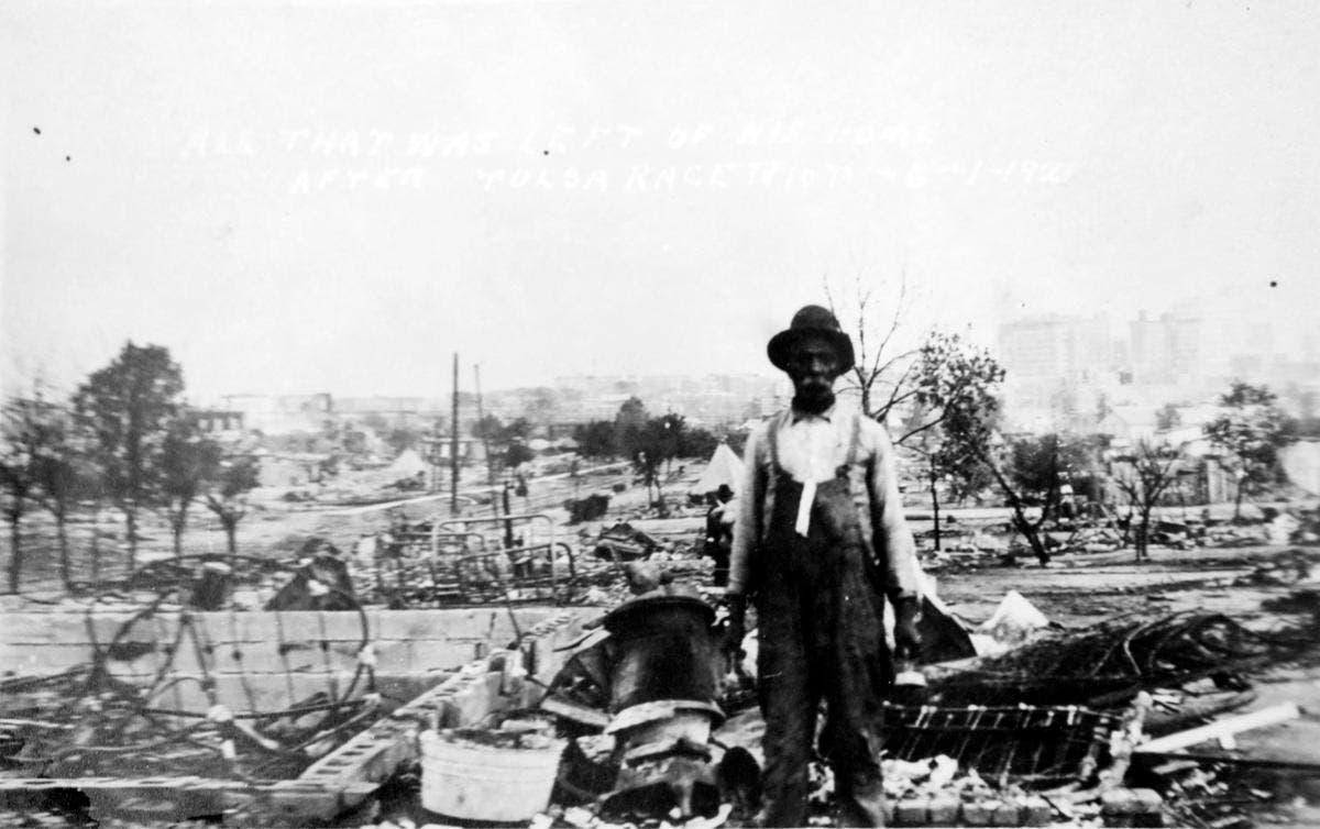 رجل من ذوي أصول أفريقية يقف أمام بقايا منزله بجرينوود