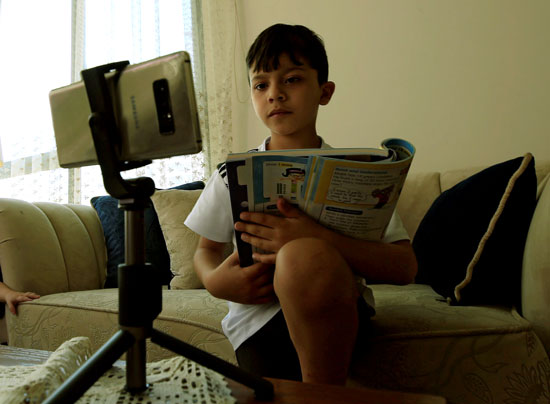 طفل يدرس عن بعد من خلال الموبايل