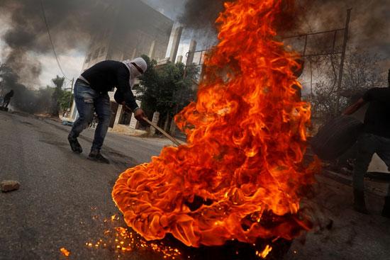 النيران تلتهم اطارات السيارات خلال المواجهة مع الاحتلال