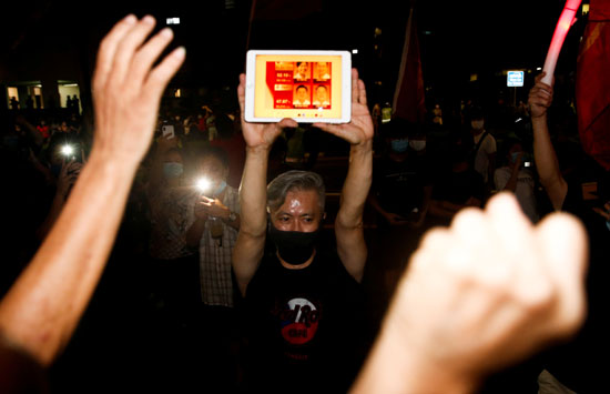 إحدى أنصار الحزب الحاكم ترفع صور قياداته بعد الفوز فى الانتخابات