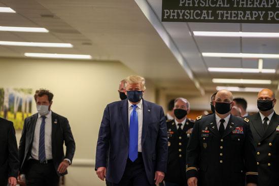 ترامب يرتدى الكمامة داخل المركز الطبى