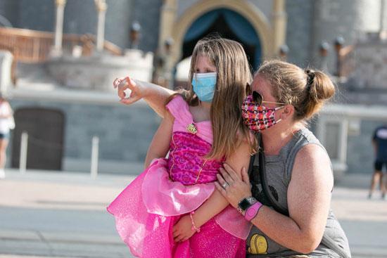 سيدة مع طفلتها داخل متنزه والت ديزنى