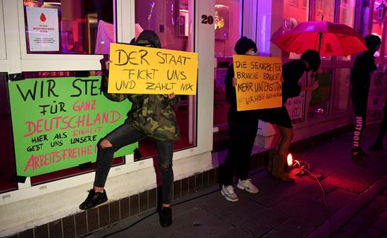 العاملات بالدعارة يحملن اللافتات