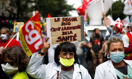 عاملة بالقطاع الصحى تحمل اللافتات