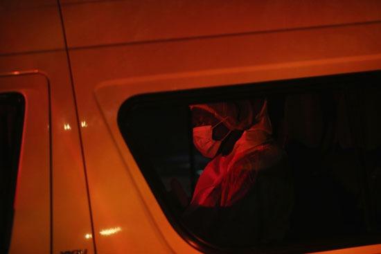 متعهدو الجنازة الذين يرتدون ملابس واقية في سيارة تحمل جثة زيندزي مانديلا