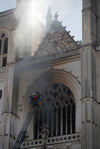 رجال الإطفاء يحاولون السيطرة على الحريق المشتعل بمبنى الكاتدرائية