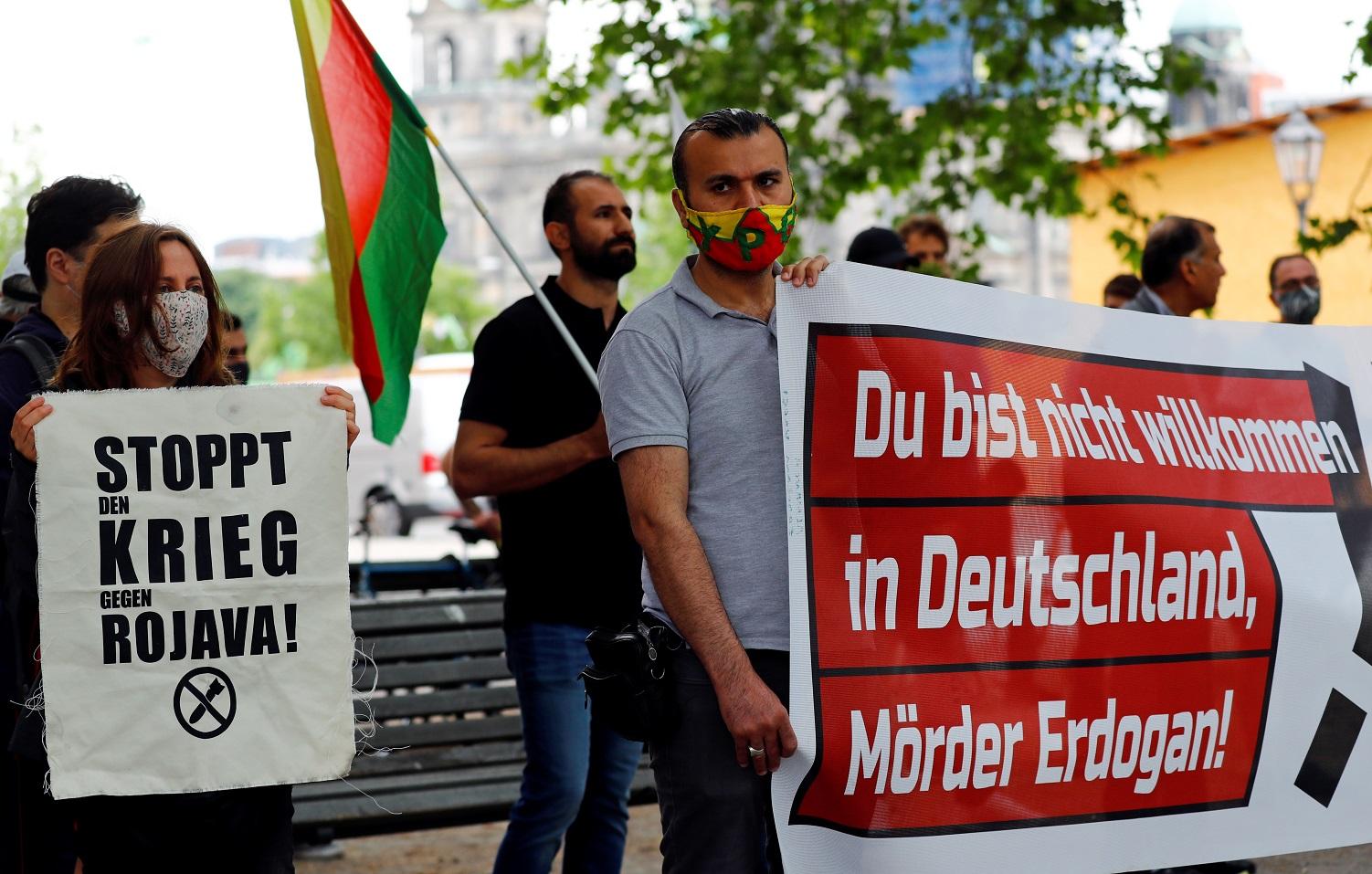 لافتة مكتوب عليها و أنت غير مرحب بك في ألمانيا ، قتل أردوغان