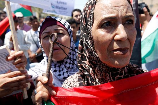 السيدات يحملن علم فلسطين خلال المظاهرة