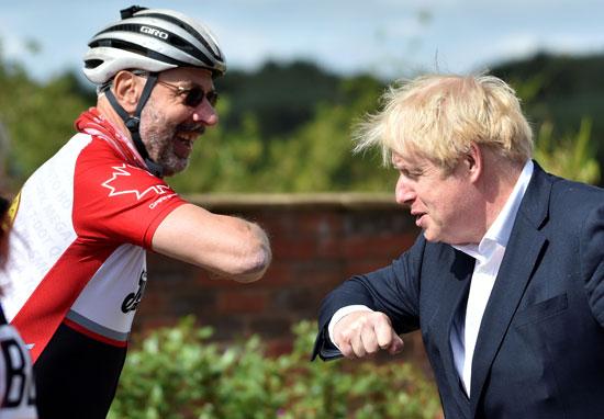 رئيس الوزراء البريطاني يصافح راكبي الدراجات