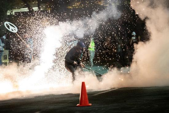 متظاهر يحاول إبعاد قنبلة الغاز باستخدام مكنسة