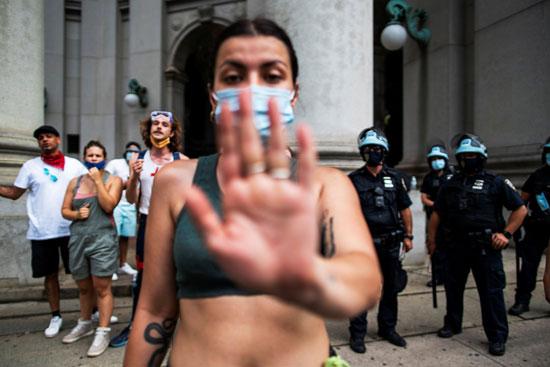 محتجة ترفع يدها لتغطية عدسة الكاميرا