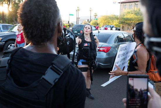 سيدة تحمل السلاح النارى فى مظاهرة بولاية أريزونا