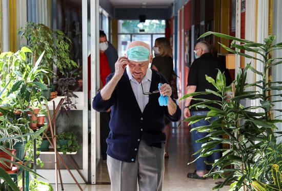 رجل يرتدى كمامته قبل الدخول إلى التصويت