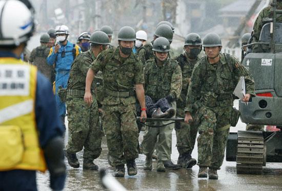 جنود من قوات الدفاع الذاتي اليابانية يحملون شخصًا تم إنقاذهم