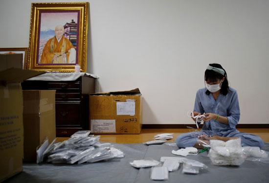 عاملة تعد الكمامات للفيتناميين المحتاجين