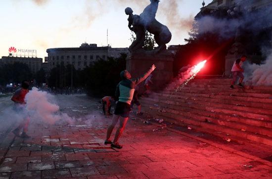 متظاهر يلقى بالشماريخ تجاه قوات الأمن الصربية