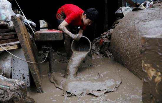 طفل يلقى بالطين والمياه من داخل منزله