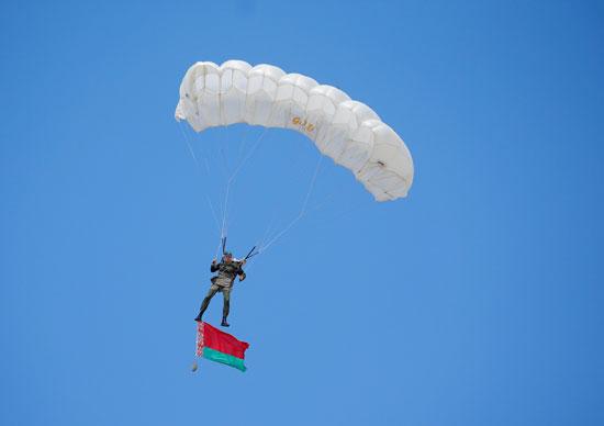 مظلي بيلاروسي بعلم وطني يؤدي خلال احتفالات الذكرى 90 للقوات المحمولة جوا في مينسك