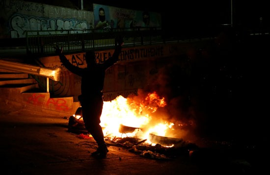 متظاهر أمام حاجز نيران صنعه المحتجون