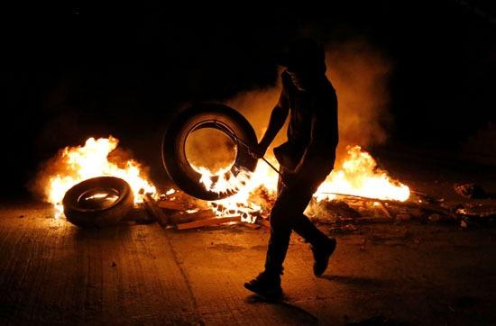 متظاهر يشعل النيران في إطار سيارة