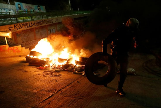 متظاهر يشارك في  صنع حاجز من النيران