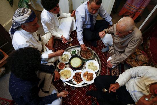 أفراد أسرة يمنية يتناولون الغداء في المنزل خلال عيد الأضحى في صنعاء باليمن