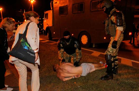 امرأة تنظر إلى رجل جريح أثناء ظهور ضباط إنفاذ القانون خلال اشتباكات مع مؤيدي المعارضة