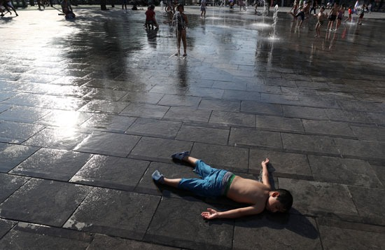 صبي يرقد على الأرض بينما يستريح الأطفال في نافورة في وسط بروكسل