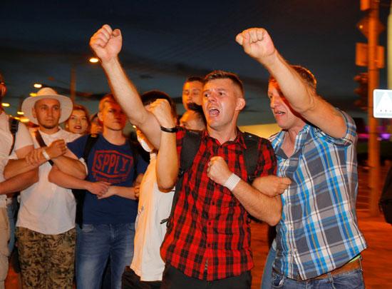 المواطنون يشيرون خلال اشتباكات مع أنصار المعارضة بعد إغلاق صناديق الاقتراع في الانتخابات الرئاسية