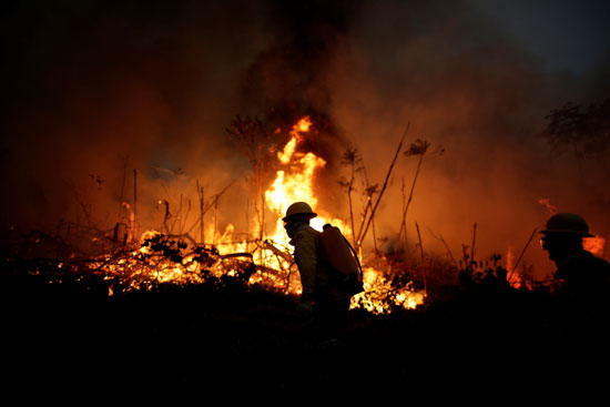 يحاول أعضاء فرقة الإطفاء السيطرة على الحرائق