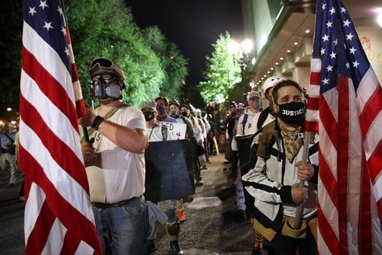 متظاهرون يحملون أعلام أمريكا
