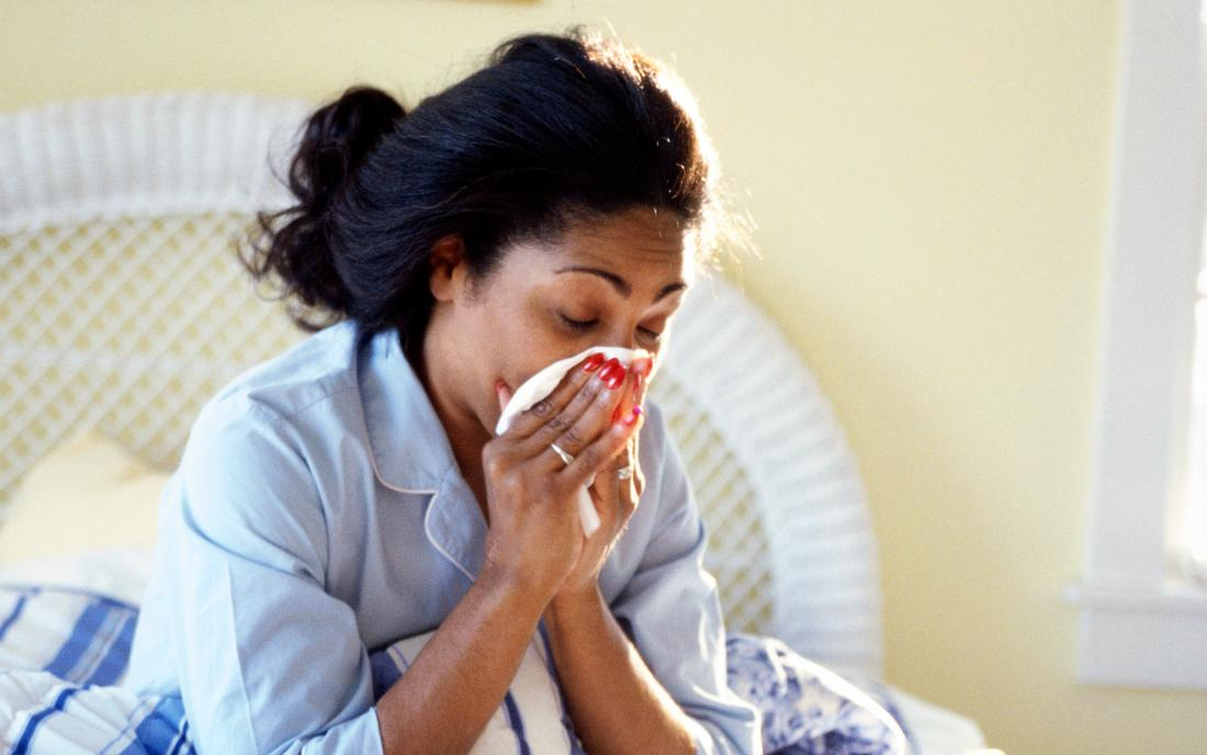 a-woman-sat-in-bed-and-blowing-her-nose-because-she-has-the-flu