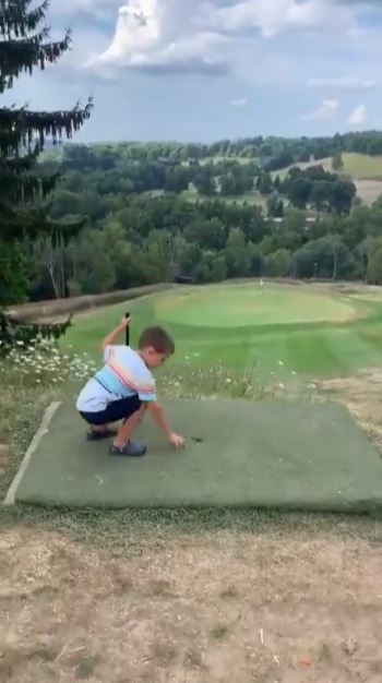 طفل يدخل كرة الجولف في الحفرة