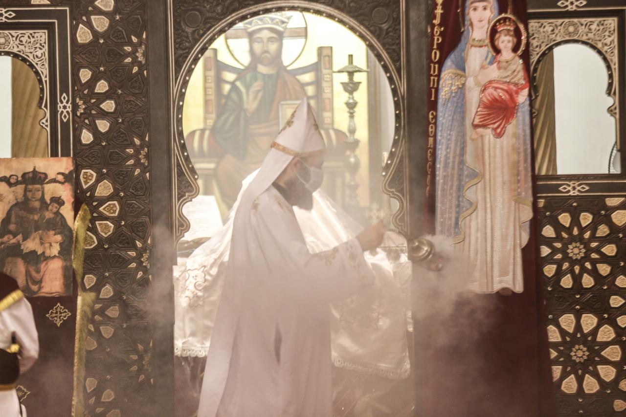 كاهن الكنيسة المعلقة يرتدى كمامة خلال القداس