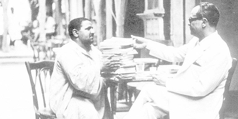 نجيب محفوظ يشترى كتبا من بائع كتب على مقهى الفيشاوى