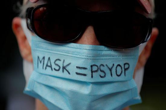 28838-أحد-المتظاهرين-يرتدي-قناعًا-مكتوبًا-عليه-Mask-=-Psyop