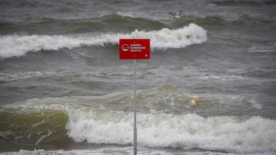 علامة الخطر مع ارتفاع الأمواج على الشاطئ