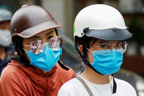 46070-نساء-يركبن-دراجة-ويرتدين-أقنعة-واقية-في-فيتنام