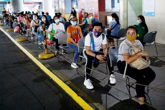 55169-ركاب-يرتدون-أقنعة-واقية-خلال-انتظارهم-حافلة-في-الفلبين
