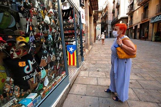 79007-امرأة-ترتدي-كمامة-وتنظر-إلى-الكمامات-المعروضة-في-شوارع-برشلونة