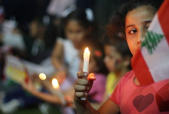 طفلة فلسطينية تحمل الشمعة تضامنًا مه ضحايا انفجار بيروت